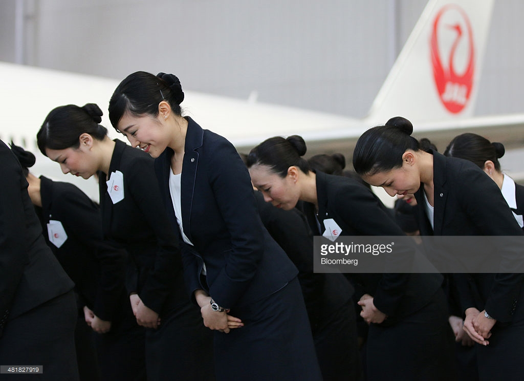 Japan Airlines Co. ( JAL) group companies' new employees bow during a welcoming ceremony at the company's hangar near Haneda Airport in Tokyo, Japan, on Monday, April 1, 2014. Photographer: Yuriko Nakao/Bloomberg